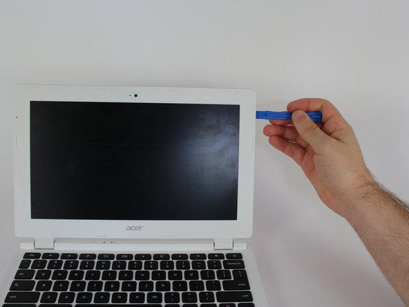 Insert the plastic opening tool into the slit on the outer edge of the laptop's screen to remove the plastic piece that borders the screen.  Work the plastic opening tool all the way around the screen until the plastic cover has been removed.