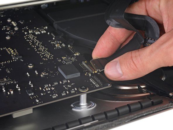 Use a pair of tweezers or your other hand to gently insert the display data cable connector into its socket on the logic board.