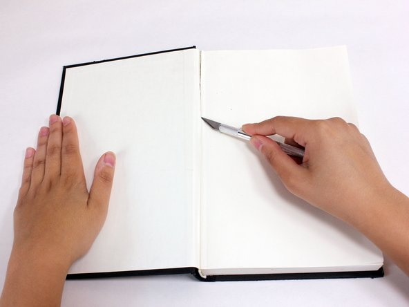 Use the Xacto knife to cut the existing endpaper along the crease.