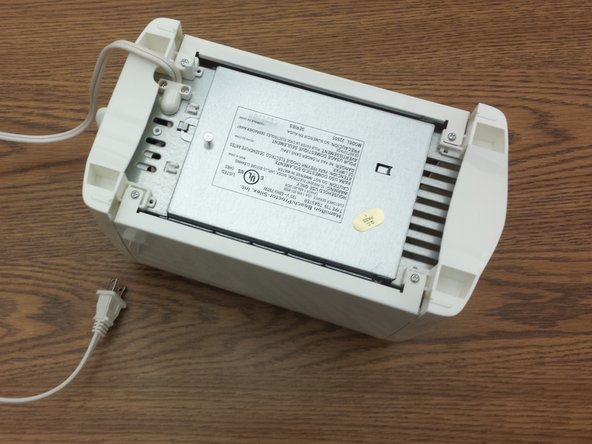 Flip toaster upside down in order to see the bottom casing with the labels and warnings now facing up.