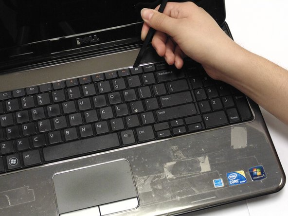 Place your spudger between the keyboard lining behind the x icon and Home keys and pull up.