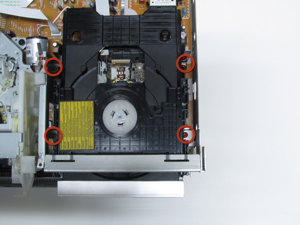 With the cover off, locate the DVD drive and remove the four red screws circled in image one.