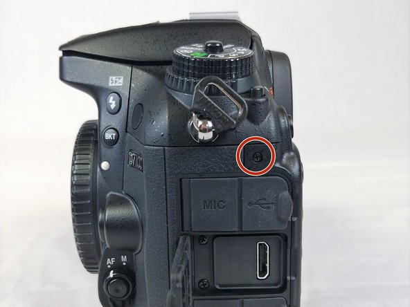 Remove the screw next to the camera strap loop.