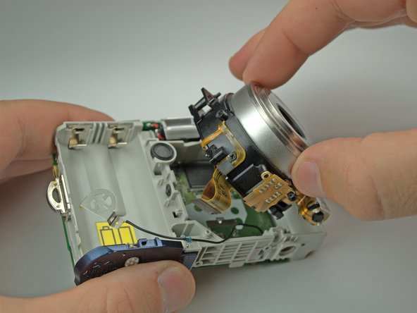 There is a screw behind flash tube holding lens. Remove it, then gently pull the lens out. Be sure that the lens's ribbon clears the motherboard.