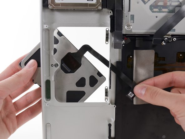Image 2/2: Once the trackpad is free of the upper case, guide the ribbon cable through the slot cut in the upper case.