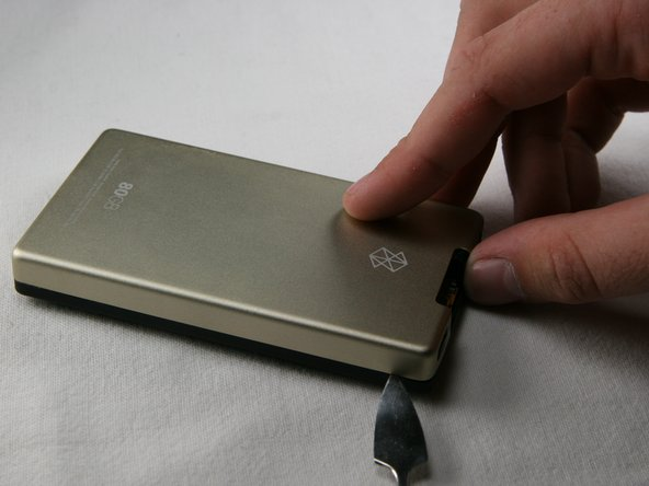 Using a metal spudger or Zune opening tool, remove the aluminum backing starting from the top. There are five clips on each side and two on the bottom.