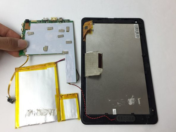 Image 2/2: The speaker connection that is on the front cover of your device is still attached to the motherboard; therefore place the motherboard close to the front cover.