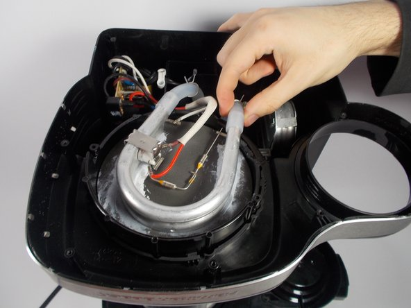 With the spring clamps moved down, slide the tubes from the ends of the large heating component. Once the ends are free, separate the component from the hot plate.