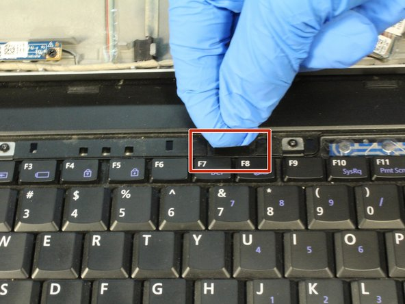 Locate the tab above the F7 and F8 keys.