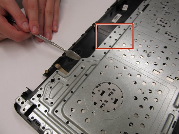 Use a metal spudger to remove the metal housing from the front panel.