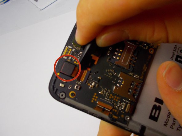 The frontward facing camera is located in the top left of the phone.  It is connected to the motherboard by a ribbon connector, and a prong system.