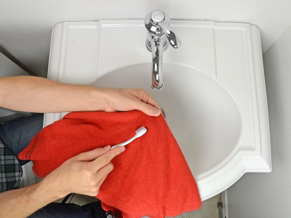Using a toothbrush, gently work the cleaning agent into the stain.