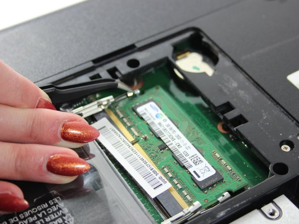 Using the curved tweezers from the Precision Tweezers Set grab and pull the metal clips away from each side of the RAM.