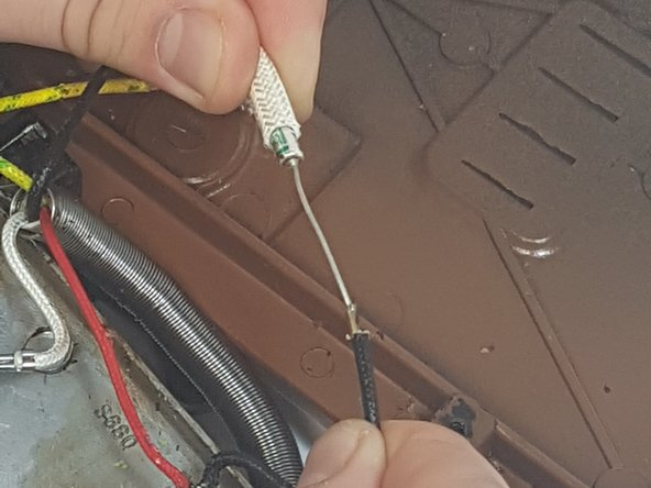 Remove the black 'rope' so you can cut the wire, using the wire cutter.