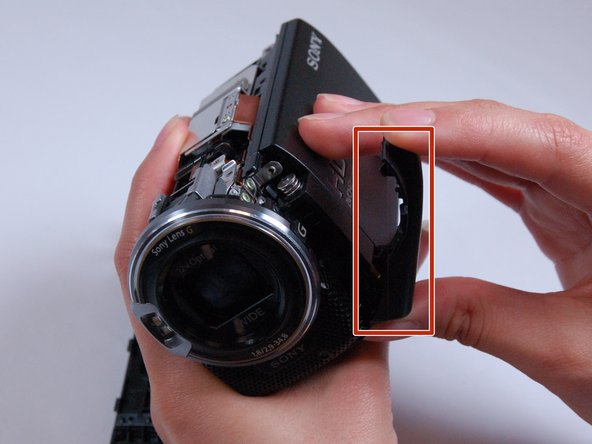 Carefully pop off the casing strip on the camera's left-hand side near the lens.