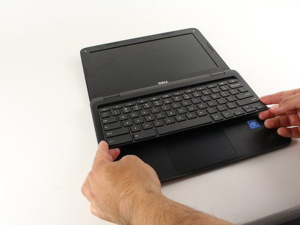Once you have separated the keyboard and the body using a spudger or plastic opening tool, use your hands to pull it away from and off of the computer.