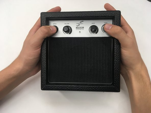 Place your thumbs on the the input jack and the tone dial. While securing the back of the silver compartment with the rest of your hands, firmly push the silver panel out of place towards the backside of the amplifier.
