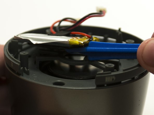 Image 2/3: Use the plastic opening tool to gently pry the battery free from the rest of the device.
