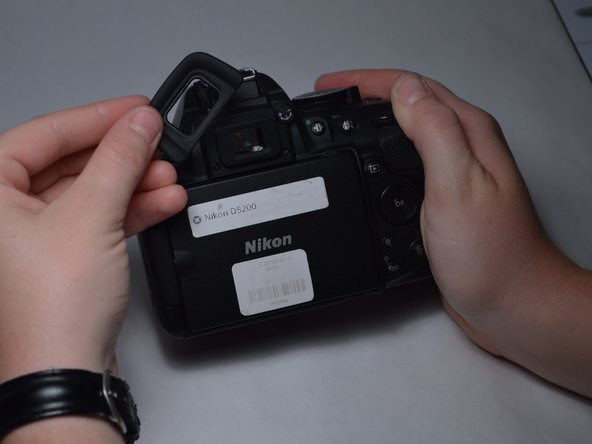 Image 2/3: Remove the three 7mm screws around the viewfinder.