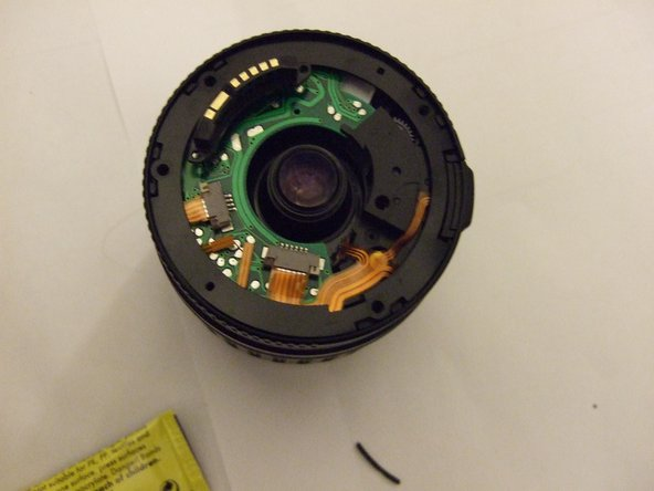 Remove the rear cover, and then remove the rubber seal (shown in place around the edge of the lens in this picture).