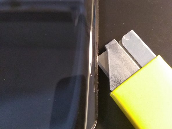 Carefully insert razor blade in between glass back plate and frame of phone.