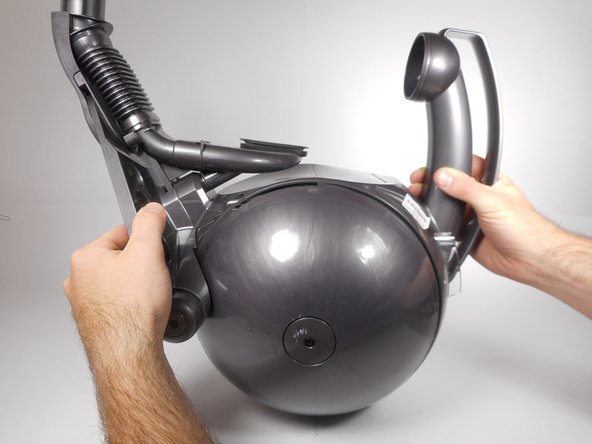 Using two hands, hold the ball housing with the handle in one hand and the steering assembly base in the other.