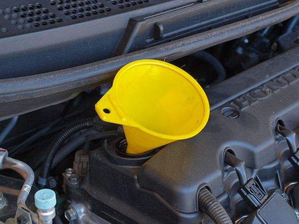 在机油 加注口中插入一个漏斗。避免加注机油的时候机油乱洒。