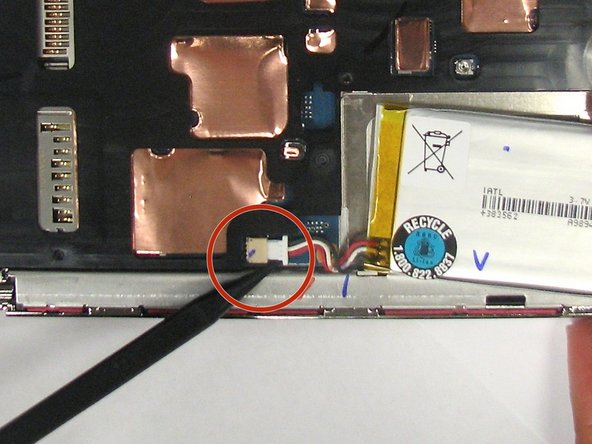 Image 1/1: Using the pointed end of the spudger, push out the white plug that is connected to the battery from its beige base.