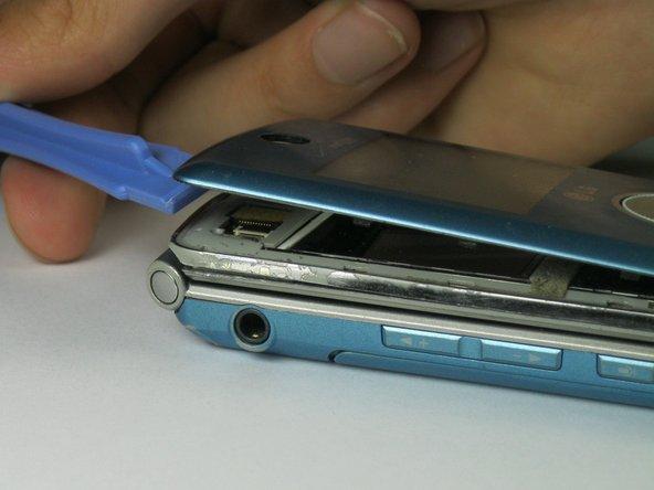 Utilisez l'outil d'ouverture en plastique pour soulever la façade avant de l'appareil.