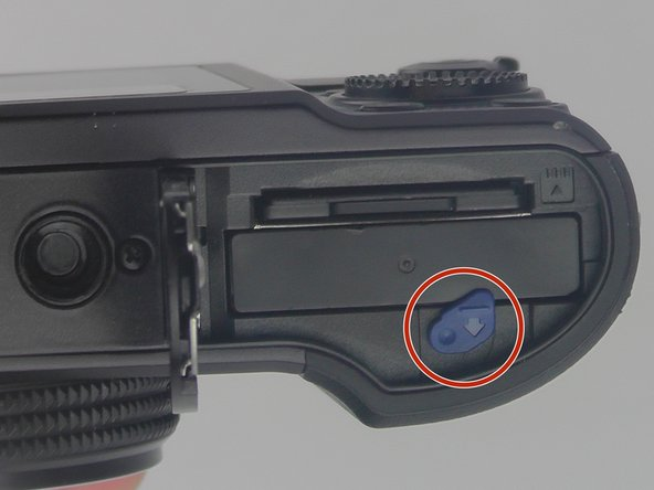 Push the blue button down in a clockwise  motion and pull out battery.