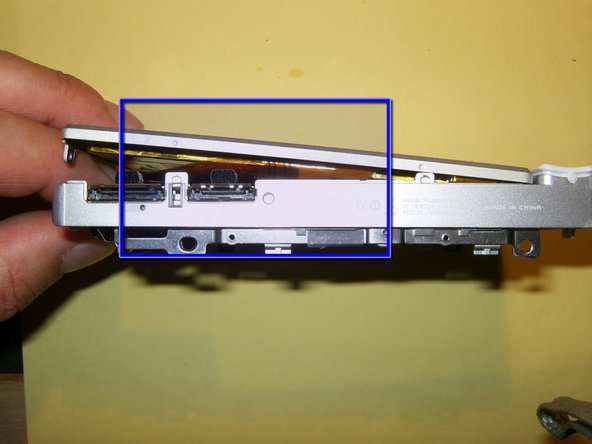 The Display is snapped into place on the side of the dock connector. This end can come loose first by using your fingernails between the frame and the display.
