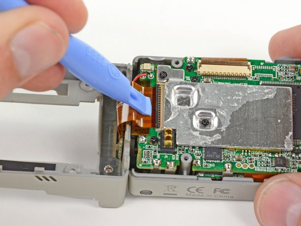 Using a plastic opening tool or your fingernail, flip up the locking tab on the SD board ribbon cable ZIF connector on the motherboard assembly.