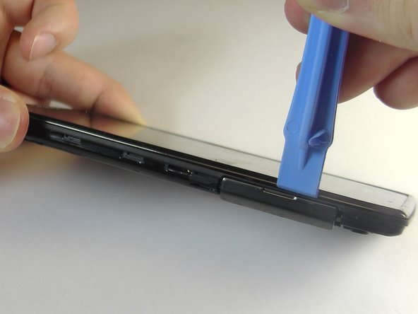 Image 1/2: Using the plastic opening tool, carefully work your way around the phone, freeing the plastic clips.