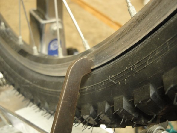 Image 2/2: Slowly tighten the calipers until they touch at some point on only one side of the rim.