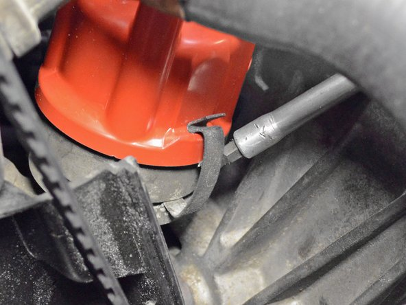 Use a flathead screwdriver to release the clip securing the distributor cap.