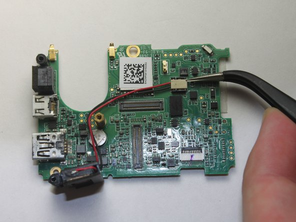 Flip the motherboard over. The speaker assembly should be loose and only connected by two wires leading to a white connector.