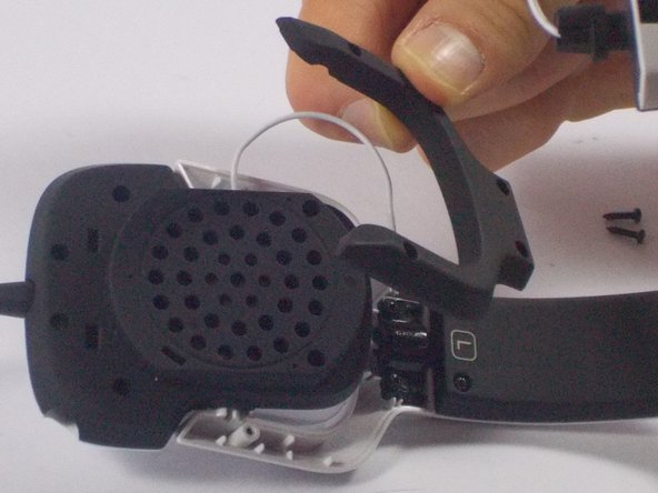 Image 2/2: Separate the black horseshoe shaped frame from the left speaker frame.