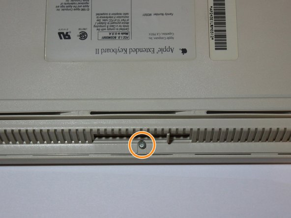 The keyboard is held in by just one philips head screw on the back! Flip over your keyboard and unscrew that bad boy.
