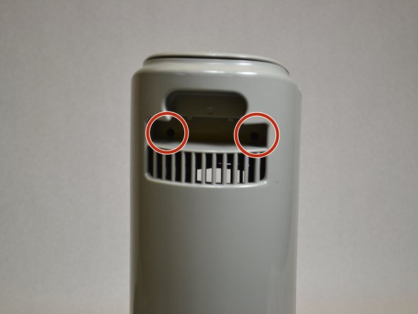 Stand the fan upright. Locate and remove the two screws near the top.