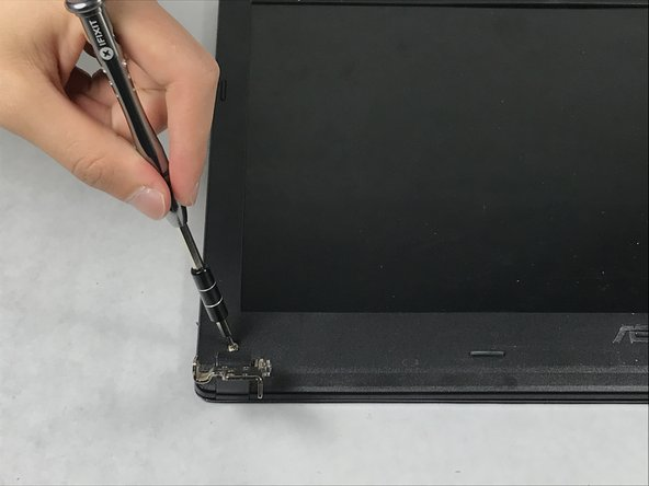 Use the Phillips #00 screwdriver to unscrew the two screws at the bottom of the laptop screen.