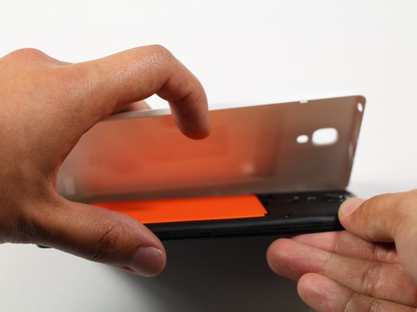 Run the plastic opening tool along the seam on the side of the phone to remove the rear casing.