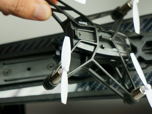 Use your pointer finger on one tab, your middle finger on the other, and your thumb on the bottom to pry the tabs away and lift the drone out of the holder.