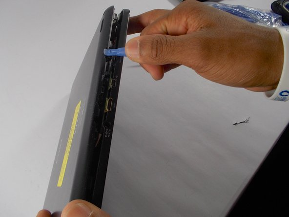Use the blue plastic opening tool to wedge the back cover apart from the front.