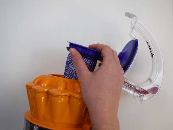 Image 2/3: Lift up the clear handle to reveal the main cylindrical filter. Pull out the purple filter piece to replace.