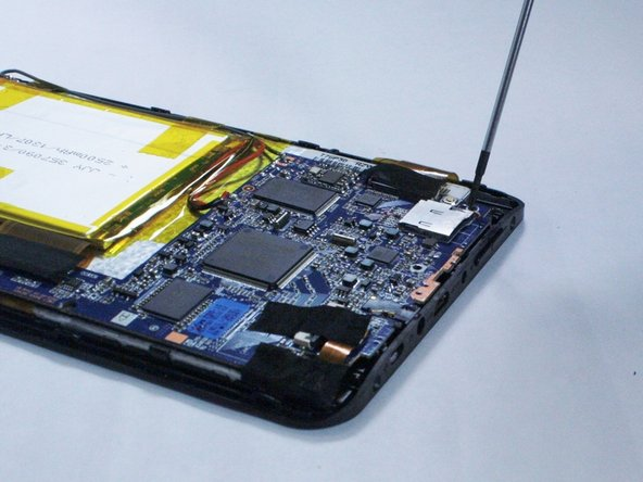 Using a plastic opening tool, gently lift the loose circuit board up and away from the back of the tablet.