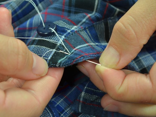 Image 2/3: Pull the thread taut, until the button lays flat on the fabric.