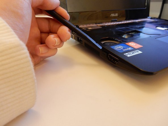 Use the spudger from the laptop to 'pop' open the track-pad base, starting from the corner shown