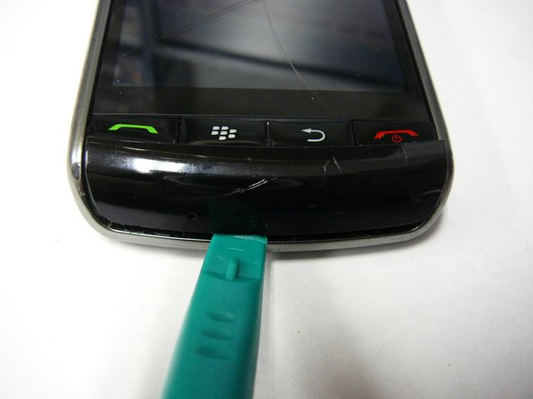 Turn the Blackberry Storm 9500 around and pry off the microphone cover at the top using a safe pry tool.