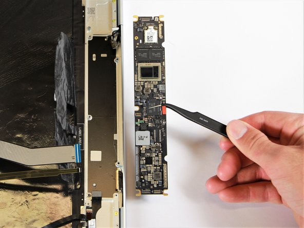 Remove the motherboard by gently lifting it out of the laptop using the needle-nose tweezers.