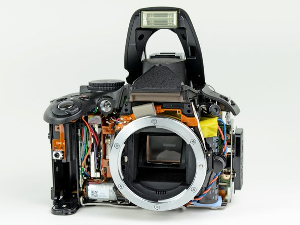Image 2/3: An electric motor (presumably linked to the shutter) can be seen next to the battery door, and the gigantic flash capacitor is housed right behind the lens release button.